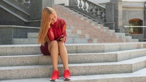 woman lookingatphone 300x169 - Is Facebook and social media making people feel more lonely, depressed and isolated?