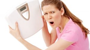 woman weightingscale 300x169 - Why am I gaining weight after quiting the gym?