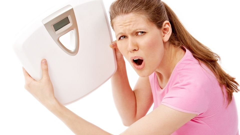 woman weightingscale - Why am I gaining weight after quiting the gym?